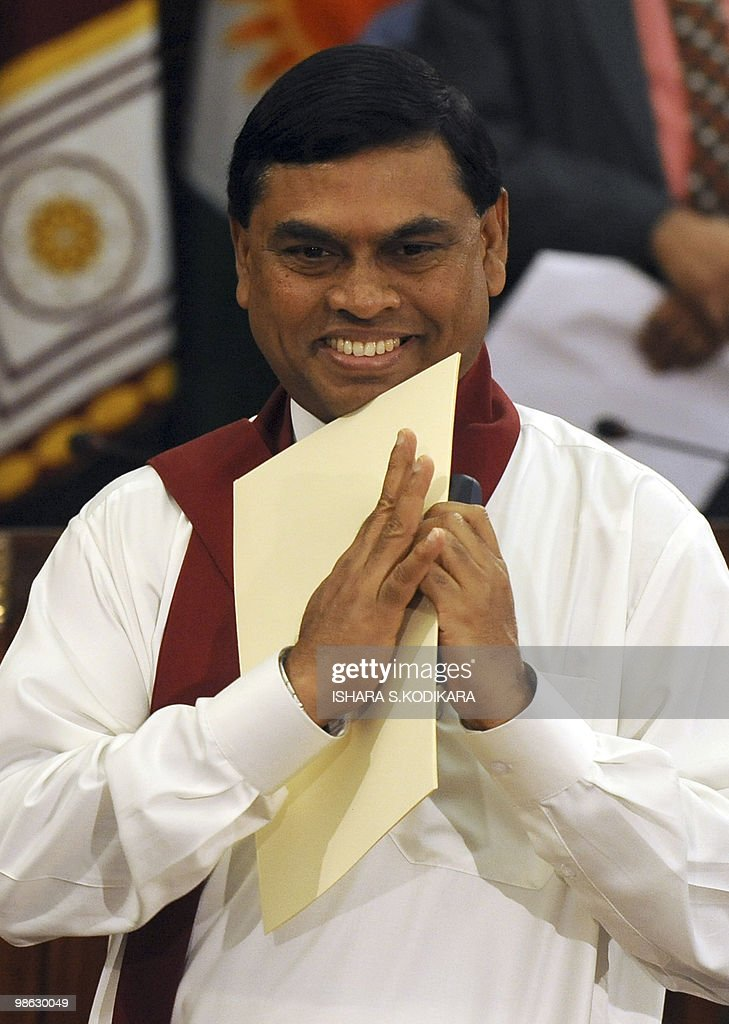 Sri Lankan President Mahinda Rajapakse's younger brother Basil Rajapakse gestures with his letter of appointment in hand in Colombo on April 23, 2010. Sri Lanka's new Cabinet was sworn in by Sri Lankan President Mahinda Rajapakse folowing his parliamentary election win on April 8. AFP PHOTO/ Ishara S