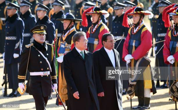 Sri Lankan President Maithripala Sirisena and South Korean President Moon JaeIn walk towards a guard of honour during a welcoming ceremony at the...
