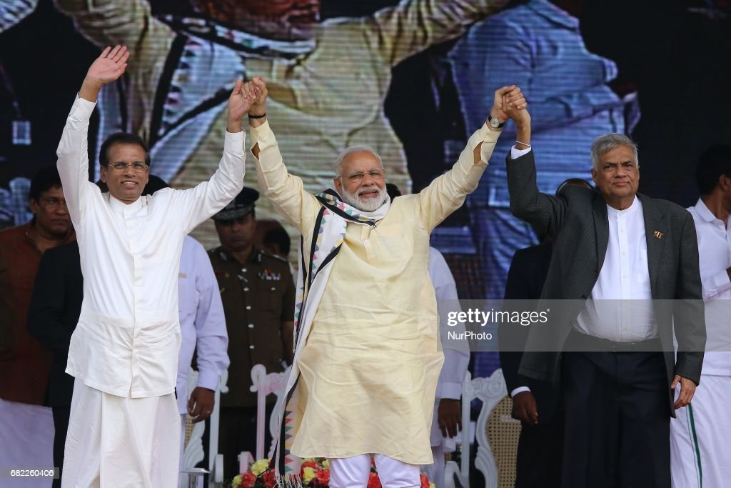 Sri Lankan President Maithripala Sirisena, left, Indian Prime Minister Narendra Modi, center, and Sri Lankan Prime Minister Ranil Wickremesinghe hold hands and wave to Sri Lankan tea plantation workers of Indian origin during a rally in Norwood, about 140 kilometers (87.5 miles) east of Colombo, Sri Lanka, Friday, May 12, 2017. During his two-day visit Modi participated in the United Nations celebration of Vesak or the day of birth, enlightenment and death of the Buddha and inaugurated a modern hospital for the benefit of tea plantation workers, ancestors of Indian laborers brought by the British from the 18th century.