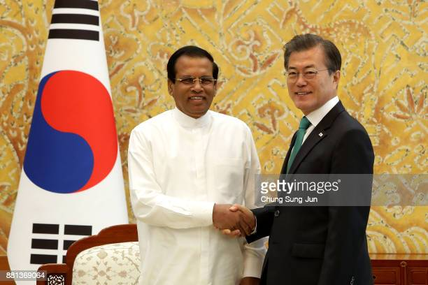 Sri Lankan President Maithripala Sirisena shakes hands with South Korean President Moon JaeIn during a meeting at the presidential Blue House on...