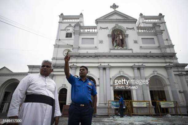 A Sri Lankan priest listens to a soldier outside St Anthony's Shrine in Colombo on April 26 following a series of bomb blasts targeting churches and...