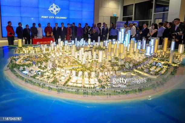 Sri Lankan prime minister Mahinda Rajapaksa, Chinese Ambassador to Sri Lanka Cheng Xueyuan and attendees look at a proposed construction model of...