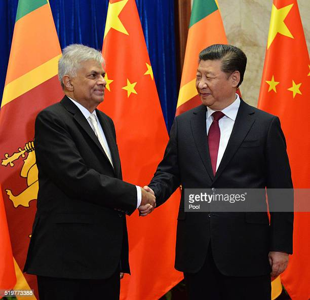 Sri Lankan Prime Minister Ranil Wickremesinghe and Chinese President Xi Jinping shake hands before a meeting at the Great Hall of the People on April...