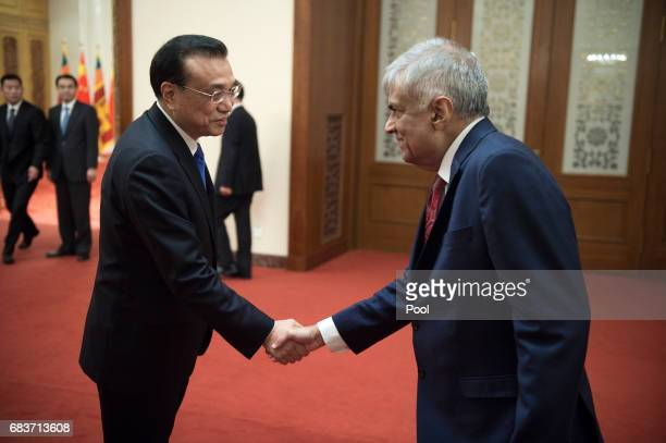 Sri Lankan Prime Minister Ranil Wickremesinghe shake hands with Chinese Premier Li Keqiang at the Great Halll of the People in Beijing on May 16 2017