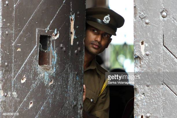Sri Lankan Prison guard looks out from a bullet riddled main door of Welikada jail in Colombo on September 14 2013 A shootout between rioting...