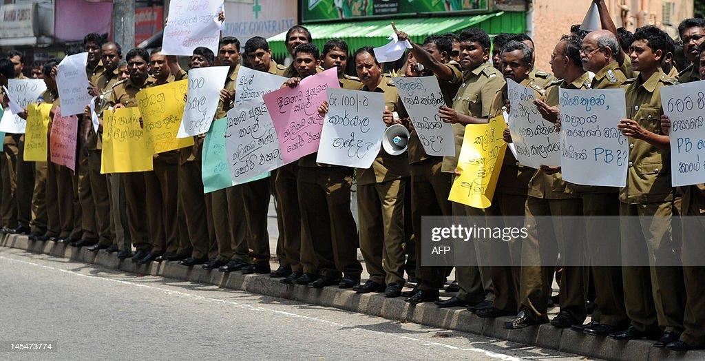Sri Lankan public health inspectors shout slogans and wave