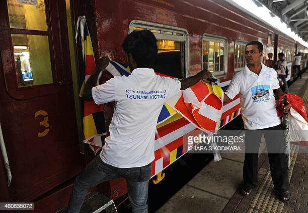Sri Lankan railway employees place flags on a train compartment that was swept away during the 2004 tsunami and later retrieved and restored as the...