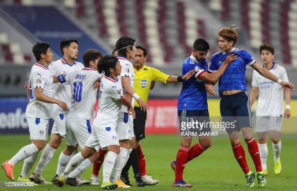 Sri Lankan referee Hettikamkanamge Perera seperates players during a disagreement in the AFC Champions League round of 16 football match between...