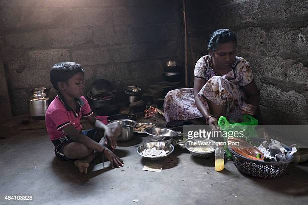 Sri Lankan refugee woman prepares lunch over an claystove in her oneroom home provided by the Government of India