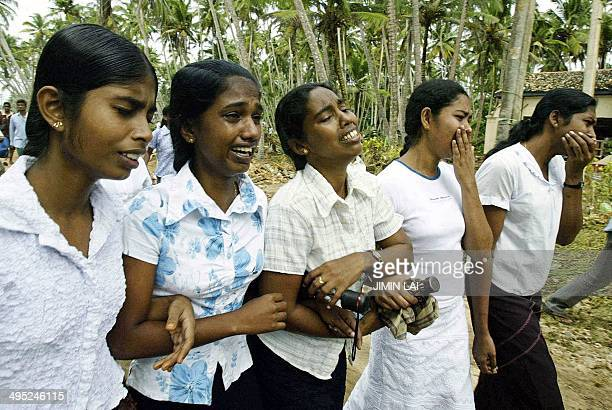 Sri Lankan relatives mourn the death of their mother and sister during a funeral ceremony in the southern coastal town of Matara 28 December 2004...