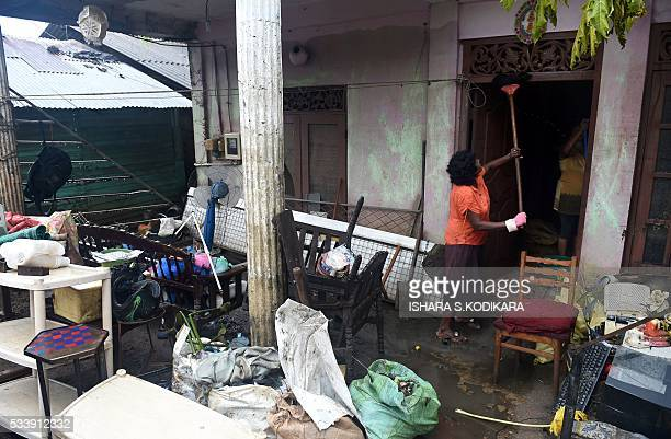 A Sri Lankan resident cleans the outside of her home following flooding in the Kolonnawa suburb of Colombo on May 24 2016 Sri Lankans camped out in...