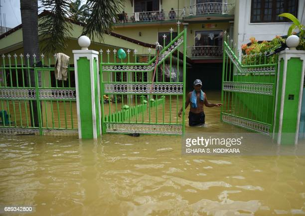A Sri Lankan resident stands in floodwaters in the suburb of Kaduwela in the capital Colombo on May 28 2017 Emergency teams rushed to distribute aid...