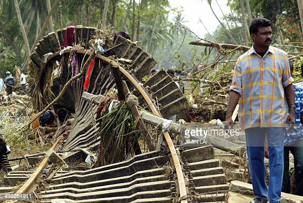 A Sri Lankan resident walks past a twisted railway track after tidal waves came crashing washing away a train in Sinigame near the tourist town of...