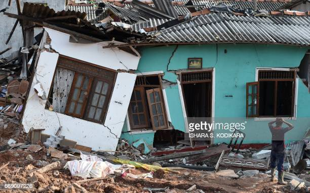Sri Lankan resident walks through damaged homes at the site of a collapsed garbage dump in Colombo on April 16 2017 Hopes of finding anyone alive...