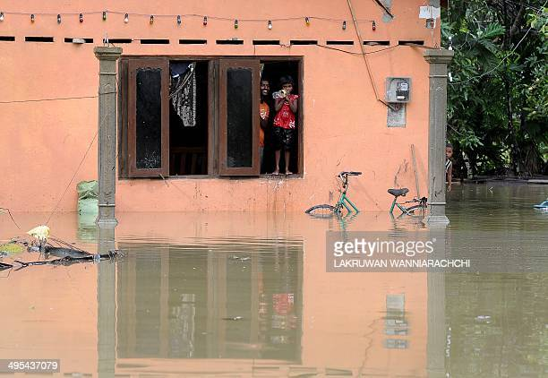 Sri Lankan residents look out of the window of their home at floodwaters in Matugama some 64 kms south of Colombo on June 3 2014 after heavy monsoon...