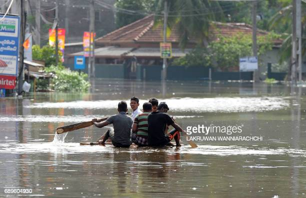 Sri Lankan residents make their way on a makeshift boat floodwaters in Nagoda in Kalutara district on May 29 2017 Sri Lanka's monsoon toll climbed to...