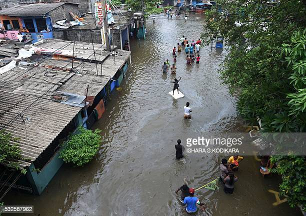 TOPSHOT Sri Lankan residents make their way through floodwaters in Colombo on May 19 2016 Sri Lankan troops recovered seven more bodies from piles of...