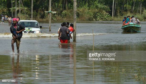 Sri Lankan residents make their way through floodwaters in Bulathsinhala in the district of Kalutara on May 29 2017 Heavy monsoon rains in Sri Lanka...