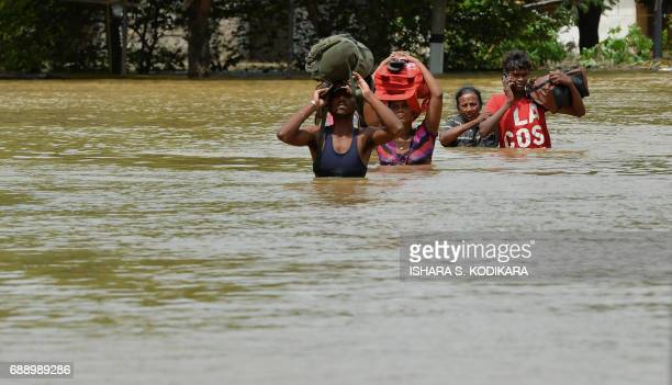 Sri Lankan residents make their way through floodwaters in Kaduwela on May 27 2017 Rainfall on May 26 triggered the worst flooding and landslides in...