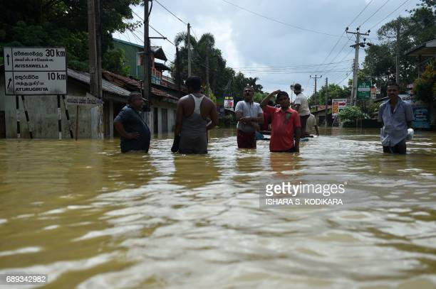 Sri Lankan residents make their way through floodwaters in the suburb of Kaduwela in the capital Colombo on May 28 2017 Emergency teams rushed to...