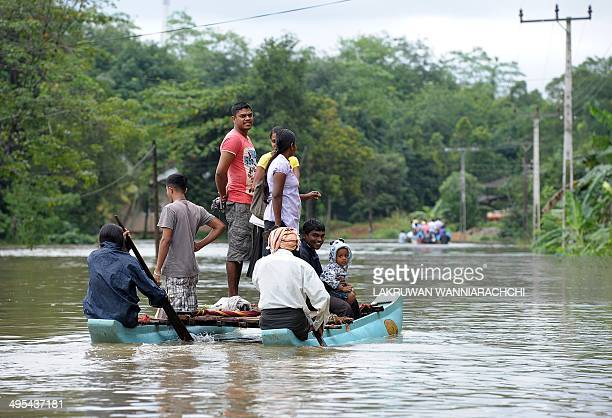 Sri Lankan residents paddle through floodwaters in Matugama some 64 kms south of Colombo on June 3 2014 after heavy monsoon rains caused havoc in the...