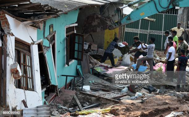 Sri Lankan residents salvage possessions from damaged homes at the site of a collapsed garbage dump in Colombo on April 16 2017 Hopes of finding...