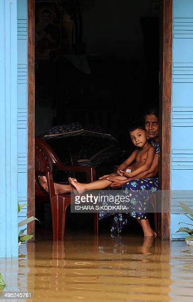 Sri Lankan residents sit in the doorway of a building surrounded by floodwaters in Welipanna on June 2 2014 Mudslides cause by heavy monsoon rains in...
