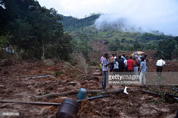 Sri Lankan residents stand at the site of a landslide caused by heavy monsoon rains in Koslanda village in central Sri Lanka on October 29 2014...