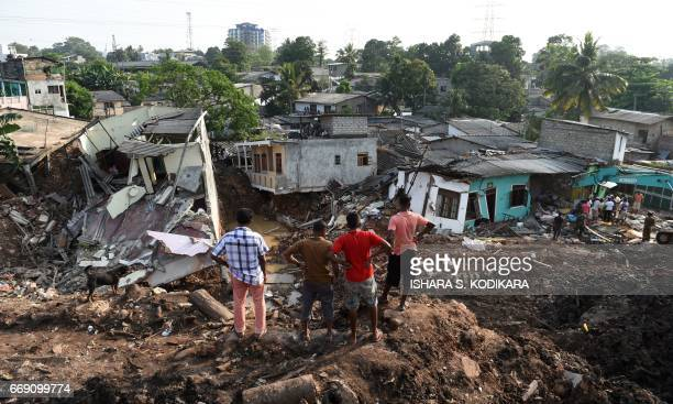 TOPSHOT Sri Lankan residents survey damaged homes at the site of a collapsed garbage dump in Colombo on April 16 2017 Hopes of finding anyone alive...