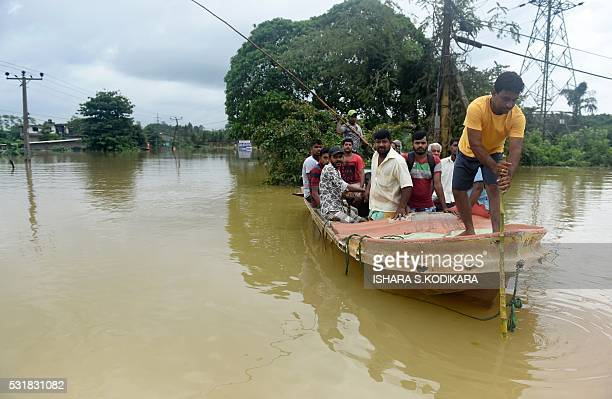 Sri Lankan residents travel by boat through the floodwaters in Pugoda about 35 kms from capital Colombo on May 17 2016 Heavy rains claimed three more...