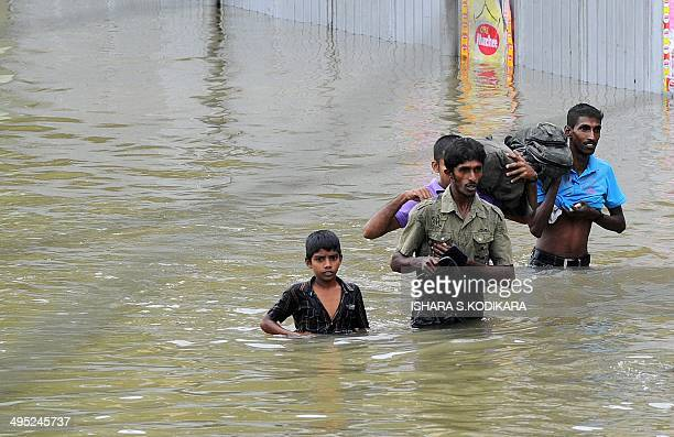 Sri Lankan residents wade through floodwaters in Welipanna on June 2 2014 Mudslides cause by heavy monsoon rains in the west and south of the island...