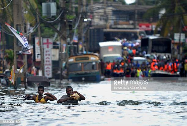 Sri Lankan residents wades through floodwaters in the Kolonnawa suburb of Colombo on May 20 2016 Desperate Sri Lankans clambered onto rubber dinghies...