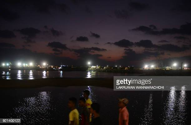 Sri Lankan residents walk past the site of a Chinesefunded $14 billion reclamation next to Colombo's main sea port on Colombo February 20 2018 China...