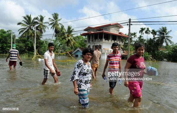 Sri Lankan residents walk through floodwaters in Dodangoda village in Kalutara on May 28 2017 Emergency teams rushed to distribute aid on May 28 to...