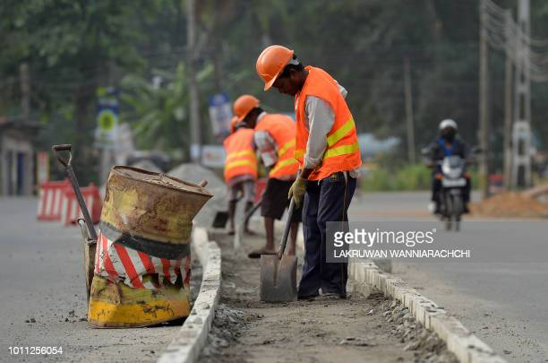 Sri Lankan road construction workers construction labourers works along a road in Colombo on August 5 2018 Sri Lanka's central bank on August 3...