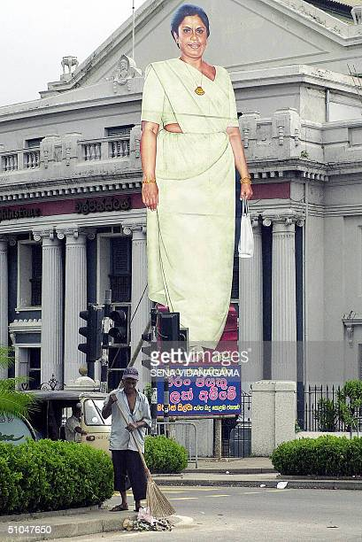 Sri Lankan roadsweeper cleans up at a traffic intersection in front of a giant cutout of President Chandrika Kumaratunga on a street in Colombo 11...