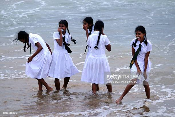 Sri Lankan school girls walk on the shores of Galle Face Beach in Colombo on December 21 2011 Sri Lanka's postwar economy grew 84 percent in the...