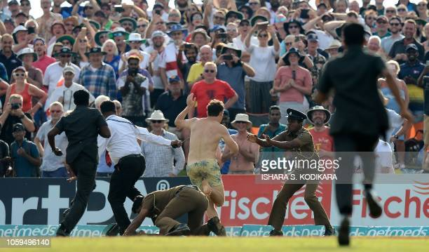 Sri Lankan security officials attempt to detain a streaker who ran onto the ground after England won the opening Test cricket match against Sri Lanka...