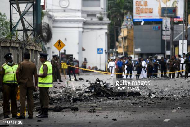 Sri Lankan security personnel inspect the debris of a car after it explodes when police tried to defuse a bomb near St Anthony's Shrine in Colombo on...