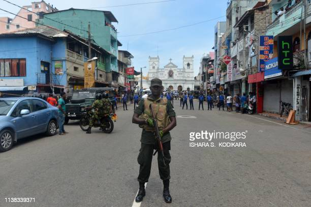 TOPSHOT Sri Lankan security personnel keep watch outside the church premises following a blast at the St Anthony's Shrine in Kochchikade Colombo on...