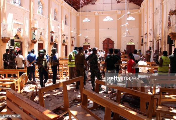 TOPSHOT Sri Lankan security personnel walk through debris following an explosion in St Sebastian's Church in Negombo north of the capital Colombo on...