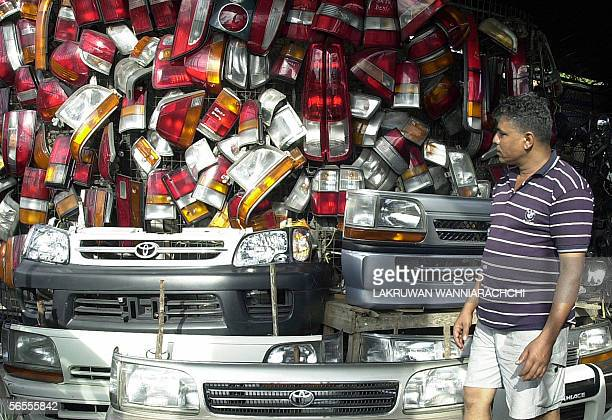 Sri Lankan shop owner D M J Dissanayake looks at a mountain of car spare parts at his shop 07 January 2006 in the northwestern Sri Lankan town of...