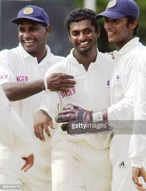 Sri Lankan skipper Sanath Jayasuriya and team wicketkeeper Kumara Sangakkara congratulate spinner Muttiah Muralitharan after Muralitharan claimed the...