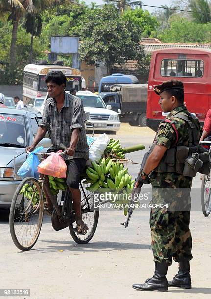 A Sri Lankan soldier looks on as traffic passes by on a street in Jaffna on April 1 2010 Sri Lanka's President Mahinda Rajapakse has reached out to...