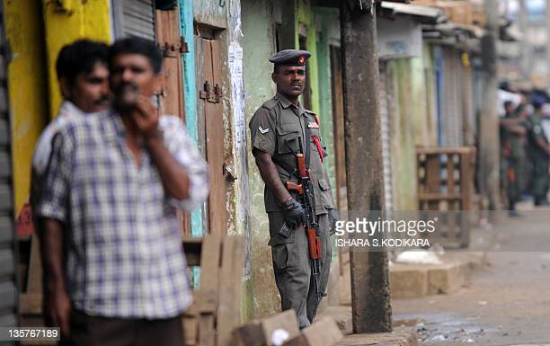 Sri Lankan soldier stands guard at a market in Colombo's main commercial district on December 14, 2011. Sri Lankan vegetable and fruit traders,...
