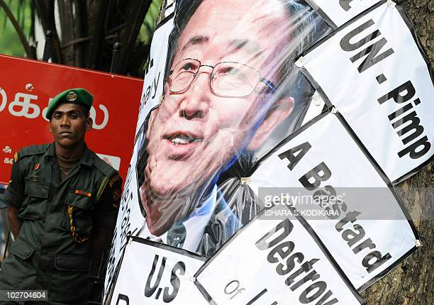 Sri Lankan soldier stands guard near a poster villfying United Nations Secretary General Ban-ki Moon during a protest rally calling for the...