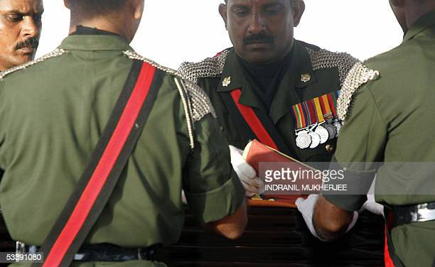 Sri Lankan soldiers fold the national flag which was draped over the coffin of slain Sri Lankan Foreign Minister Lakshman Kadirgamarat a cremation...