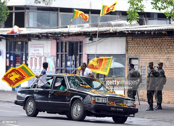 Sri Lankan soldiers look on as youth drive past with their national flag celebrating on the street in Colombo on May 20 2009 Sri Lanka marked victory...