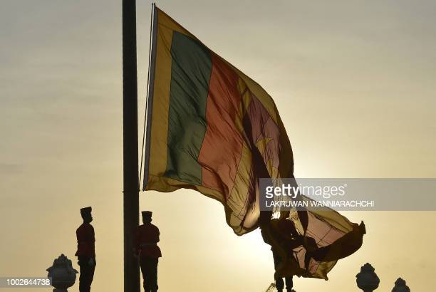 Sri Lankan soldiers stand at attention as their national flag is lowered as part of a daily ceremony at the Galle Face Green promenade in Colombo on...