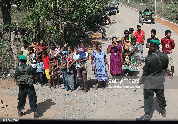 Sri Lankan soldiers stand guard next to a road as people wait to see the President President Mahinda Rajapaksa travel on board a train en route to...